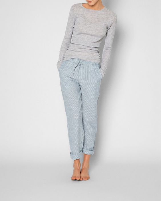 striped blue pants and a light grey shirt with long sleeves