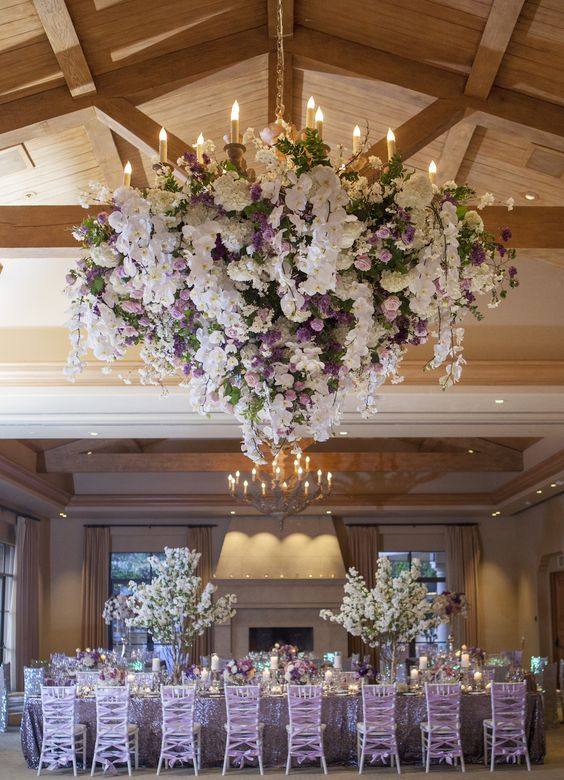 an elegant floral chandelier was embellished with lush white and lavender flowers