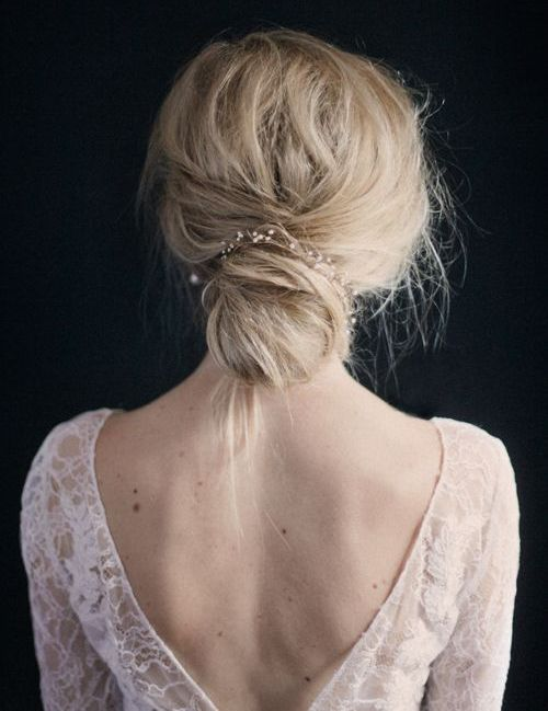 delicate wedding hairstyle with a bun and a crystal hairpiece