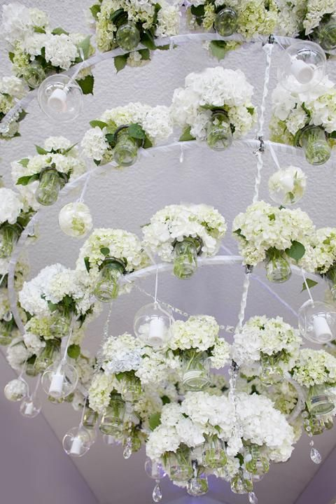 oversized white hydrangea chandelier with flowers in jars to keep them fresh
