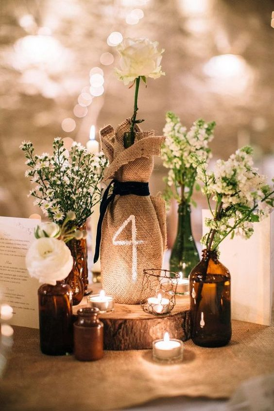centerpiece with small bottles with flowers and tealights, table number on the burlap sack