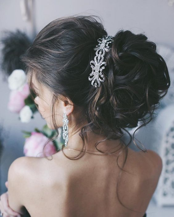 messy updo for long hair with a crystal hairpiece