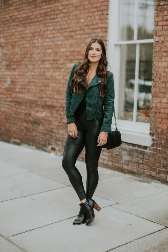 black tank top, black faux leather leggings, black heeled booties and a green faux suede moto jacket