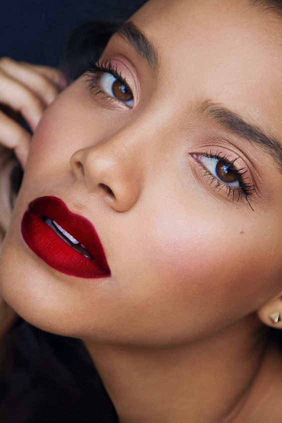 darker complexion and a bold red lipstick