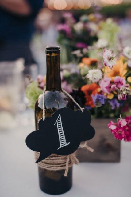 wine bottles with chalkboard table numbers tied with twine