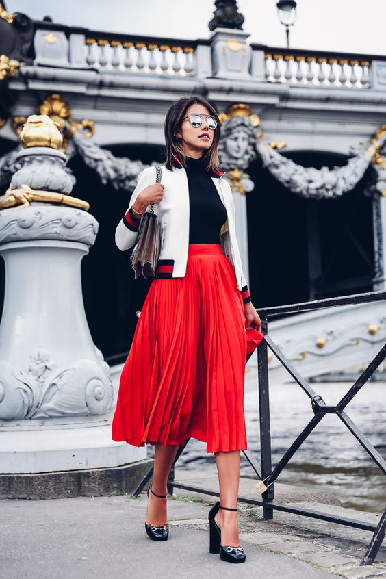 red pleated midi skirt, a black turtleneck, a white bomber jacket and heels