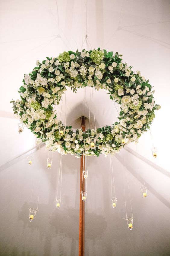 large green and white floral chandelier with crystal candle holders for a tented reception