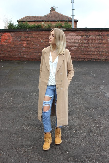 With midi coat, white blouse and distressed jeans