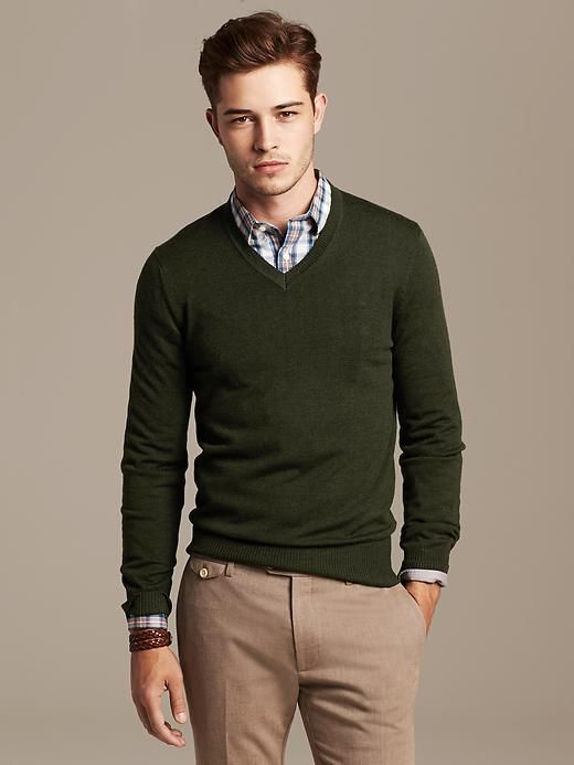 dark green pullover, a checked shirt and light brown trousers