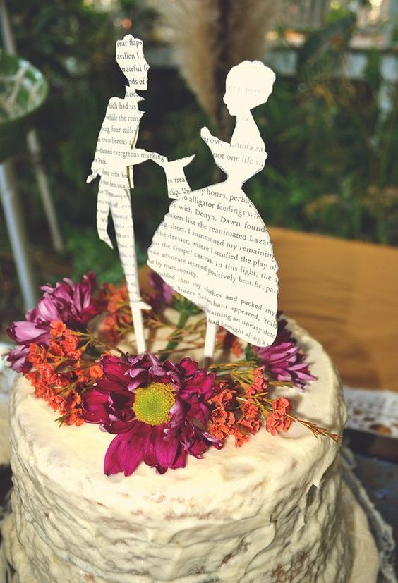 wedding cake topped with fresh flowers and cutout silhouettes from book pages