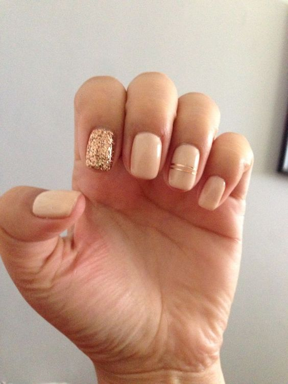 neutral nails with a gold glitter accne tone and gold stripes