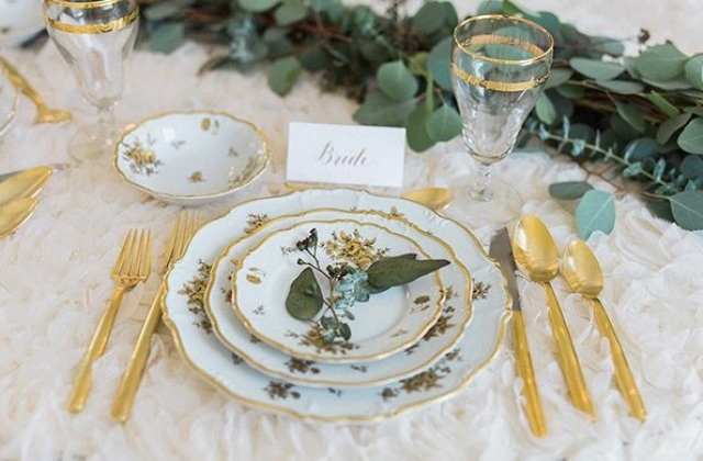Gilded details, patterned porcelain and greenery made the table setting gorgeous
