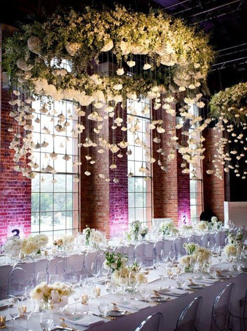 giant white flower chandelier with hanging flowers from above for an all-white modern reception