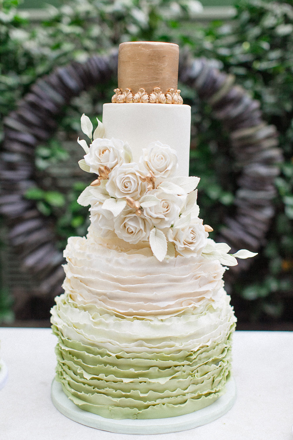 gold and green wedding cake with sugar flowers - photo by Roberta Facchini Photography http://ruffledblog.com/herbarium-inspired-wedding-ideas