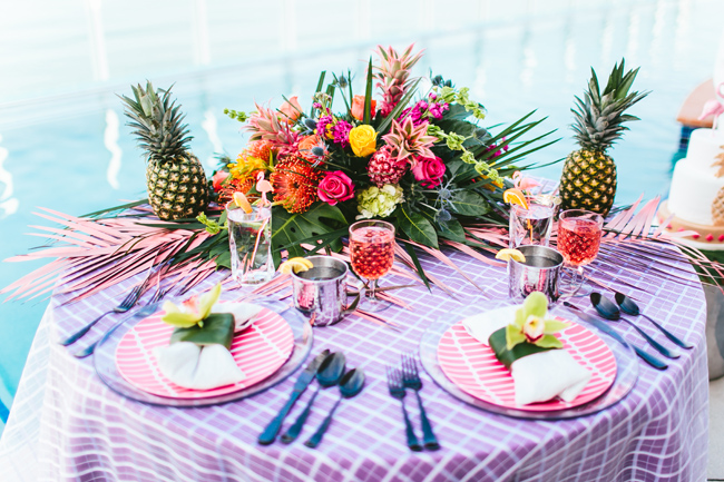 The sweetheart table was decorated in super bold tropical colors, with tropical flowers and palm leaves and pineapples for decor