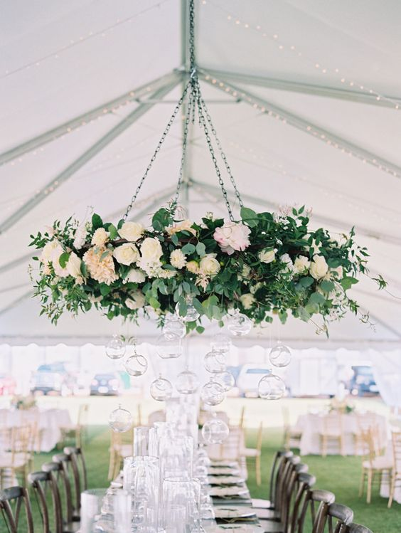 romantic white flower chandelier with greenery for a wedding reception