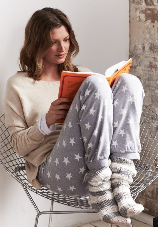 star-patterned trousers and a neutral sweatshirt, striped socks