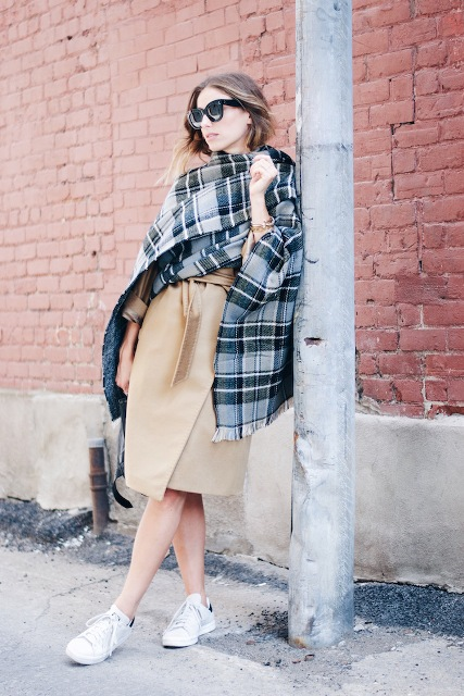 With white sneakers and oversized plaid scarf
