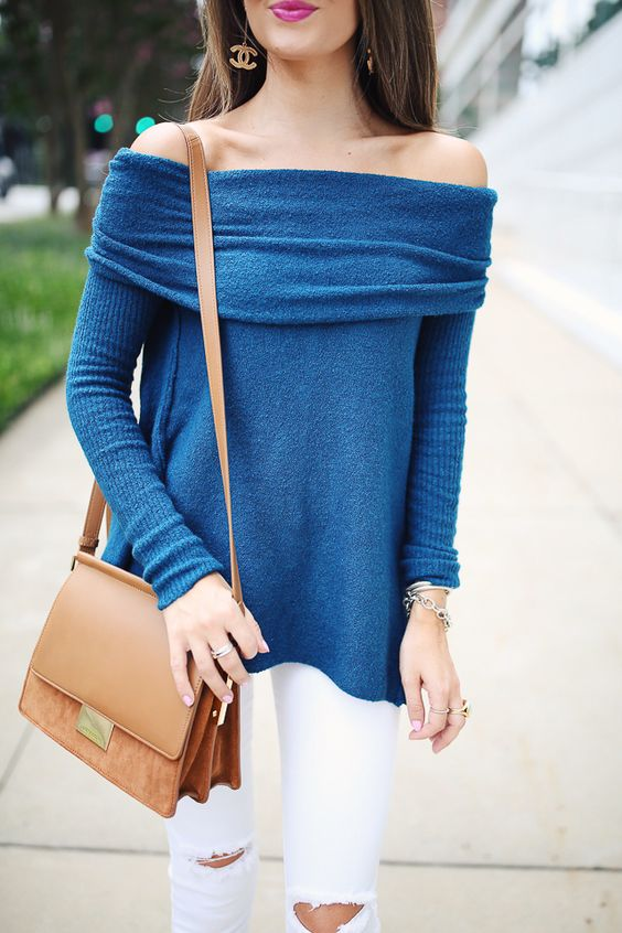 white denim and a blue sweater with a tan bag