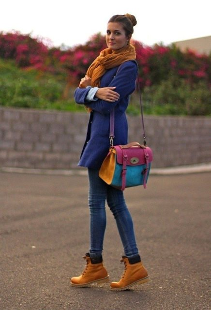 With blue coat, orange scarf, jeans and colorful bag