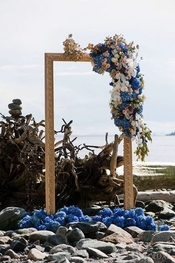 Greek wedding altar with a gilded frame and blue flowers