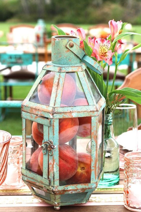antique patina lantern with real peaches inside as a centerpiece