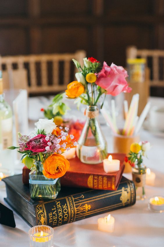 books with candles and flowers in vases
