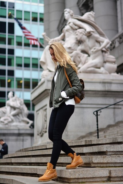 With green army jacket, skinnies and backpack