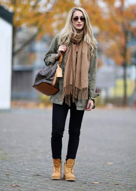 With green army shirt, oversized scarf and black pants