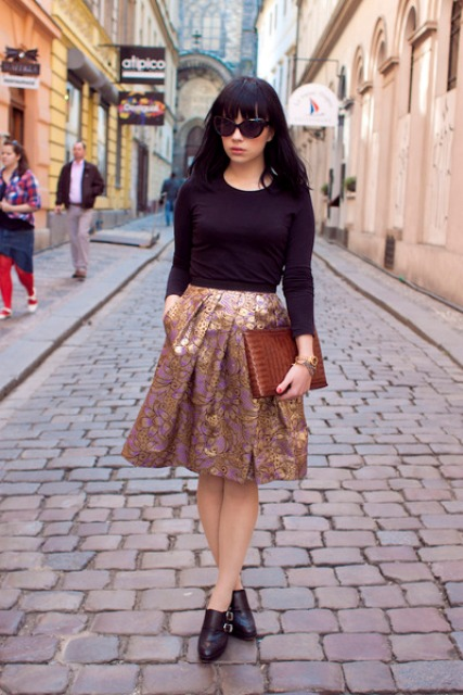 With black shirt, ankle boots and brown clutch