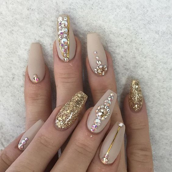 neutral nails with gold accent nails with large beading