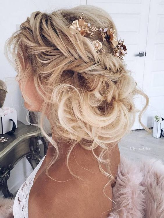 braided messy updo with a flower hairpiece will be great for boho brides