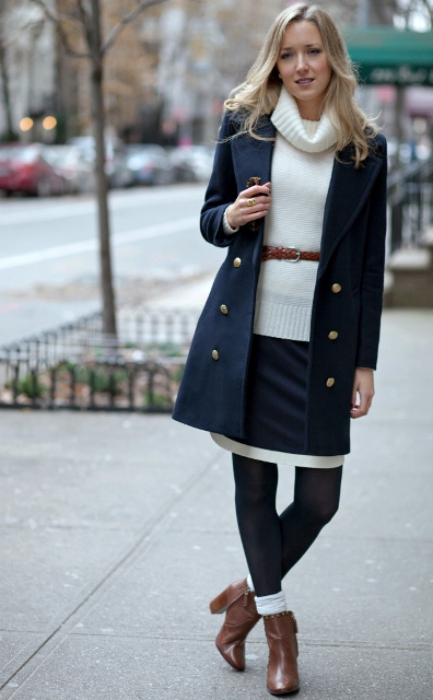 With double breasted navy blue coat, brown ankle boots and leather belt