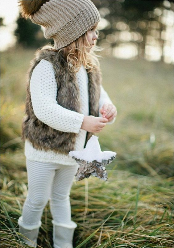 white kint sweater, leggings, a faux fur vest and a beanie