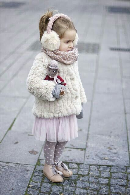 a faux fur coat and earmuffs, a tulle pink skirt, polka dot tights and boots