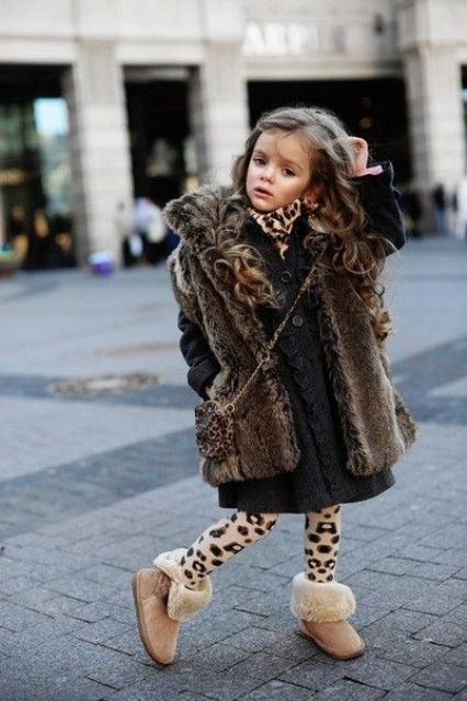 a fur coat, a knit black dress, leopard tights and faur ugg boots
