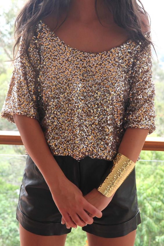 sequin shirt with a low cut, black leather shorts and a metallic bracelet