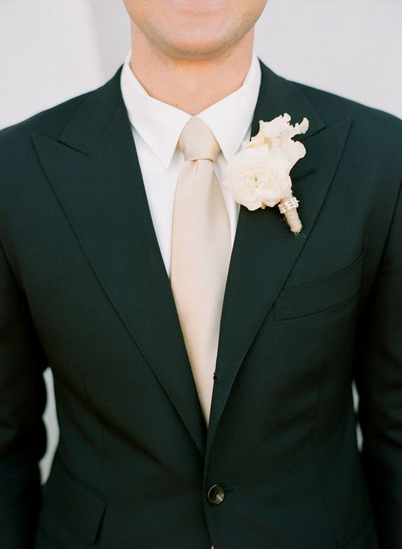 a black suit, a blush tie and an ivory shirt and boutonniere