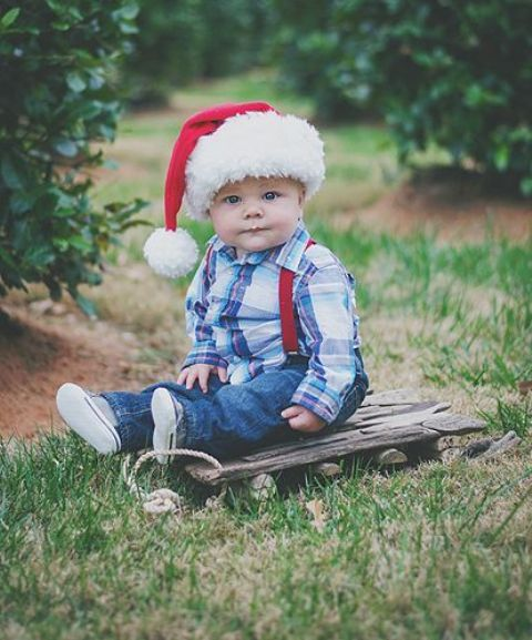 jeans, a plaid shirt, sneakers and a red Santa hat