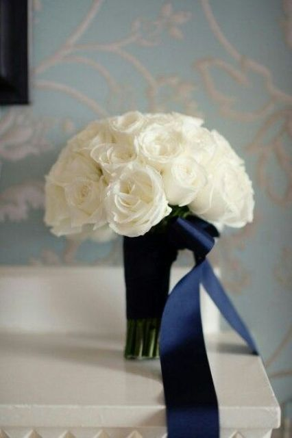 elegant bouquet of white roses and navy ribbon