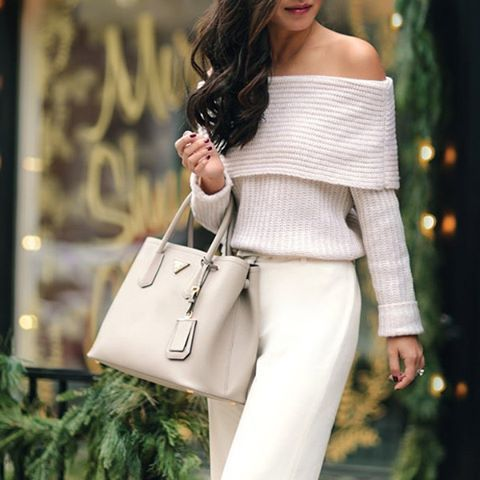 white pants, an off the shoulder sweater and a neutral bag