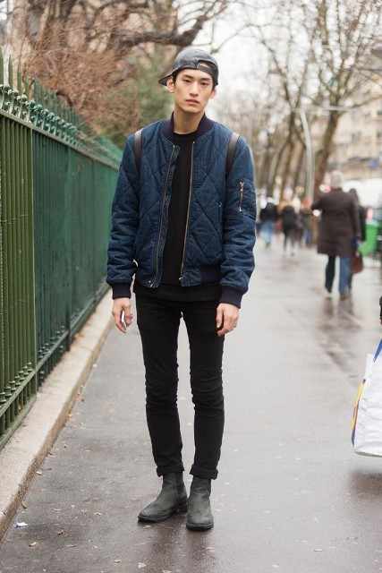 With black sweatshirt, cuffed pants, boots and cap