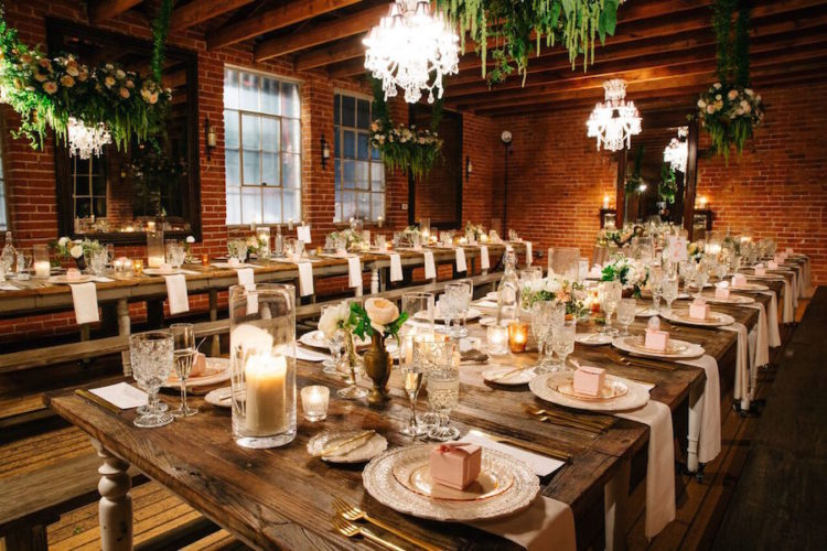 The reception was lit with candles and refined chandeliers, rustic wooden tables and benches looked contrasting with brick walls