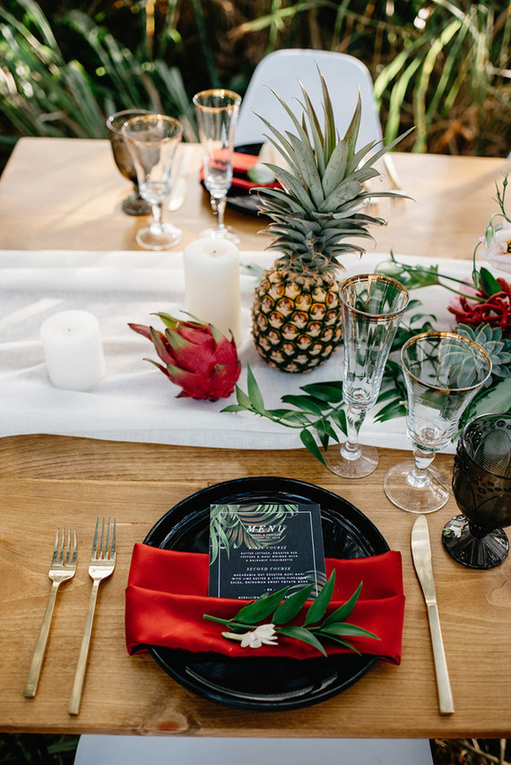 The table runner featured white fabric, tropical fruit and leaves