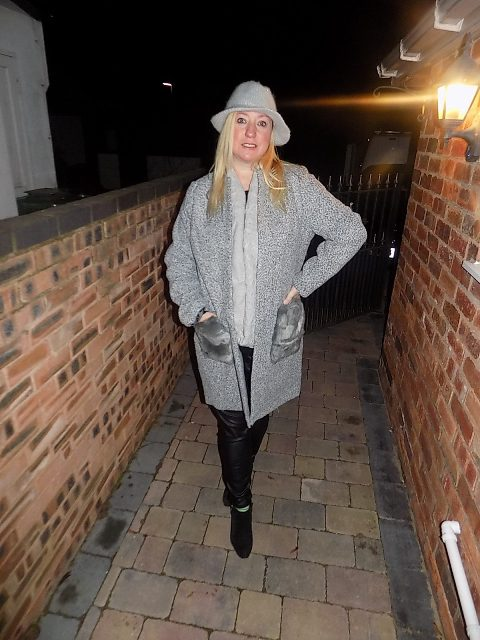 With leather pants, gray shirt, felt hat and ankle boots