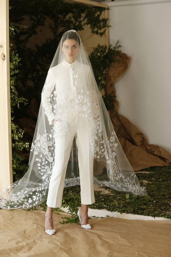 copped ivory pants and a shirt, white floral heels and a long veil