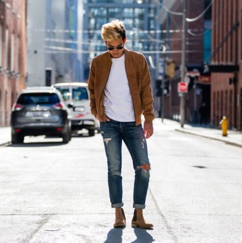 With white shirt, brown jacket and distressed jeans