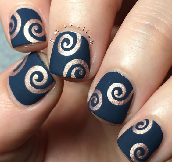matte navy nails with metallic copper swirls