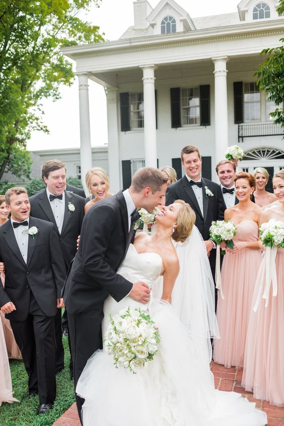 groomsmen in black tuxedos and bridesmaids in blush gowns