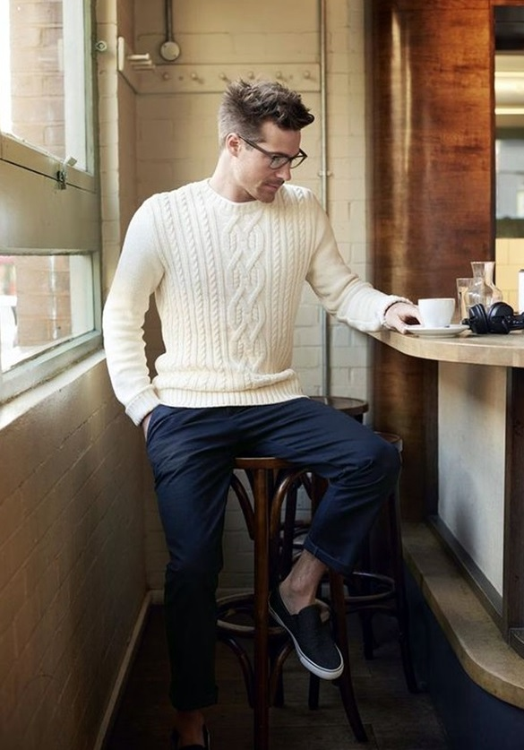 navy pants, a white cable knit sweater and slip-ons